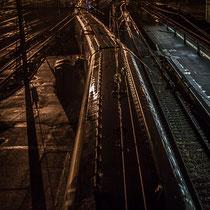 Extérieur nuit. Passage d'un TGV, sans arrêt à la Gare Saint-Jean, Bordeaux. Wagons et rails