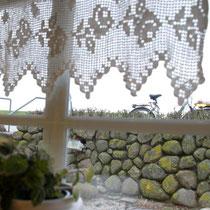 Blick auf die Steinmauer, weil das Café tiefer als die Straße liegt