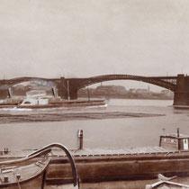 Blick von der linken Rheinseite in südöstliche Richtung. Unter dem Brückenbogen erkennbar Wanheimerort mit den Kabelwerken. Auf dem Rhein Schiffsverkehr (Raddampfer) und eine Floßeinheit. Quelle: Stadtarchiv Duisburg