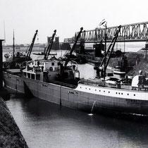 """Rhein-See-Schiff """"Homberg"""" aus der Haniel-Flotte 1939, von der 1. Rheinbrücke existieren nur noch die markanten Brückentürme."""