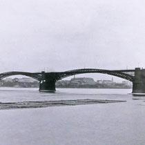 Blick von der linken Rheinseite in südöstliche Richtung. Unter dem Brückenbogen erkennbar Wanheimerort mit den Kabelwerken. Auf dem Rhein eine Floßeinheit. Quelle: Stadtarchiv Duisburg