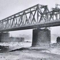 Die neue Eisenbahnbrücke, im Bildhintergrund noch sichtbar die alten Pfeilerreste. Quelle: Stadtarchiv Duisburg