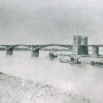 Blick von der rechten Rheinseite über die Mündung des Kultushafen auf die 1. Rheinbrücke. Der runde Brückenpfeiler trägt die Drehbrücke zur Unterbrechung der Eisenbahnstrecke. Quelle: Stadtarchiv Duisburg