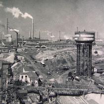 Firmenansicht 60-70er Jahre, im Hintergrund die Brücke der Solidarität. Große Teile des nördlichen Firmengeländes dienten als Schlackenlagerflächen.I Hintergrund Brücke der Solidarität, Baubeginn 1945, Eröffnung 1950.