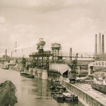 Blick von der Eisenbahnbrücke auf den Nordhafen der Niederrheinischen Hütte in Duisburg-Hochfeld. Im Hintergrund Brücke der Solidarität, Baubeginn 1945, Eröffnung 1950.