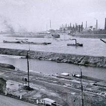 Blick über den Südhafen, Hafenmole und den Rhein in Richtung der Krupp Hüttenwerke und Hafeneinfahrt. Heute Logport-Hafen.