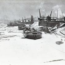 Geschlossene Eisdecke im Südhafen, Ruhender Schiffsverkehr, Bergung und Verladung von Holzflößen stark eingeschränkt