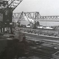 Gussblöcke aus Stahl (links unten im Bild) zur weiteren Verladung bereit liegend. Im Bildhintergrund Verladetätigkeit vom Schiff auf Waggon.