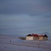Ein vom Winter gezeichnetes Wohnhaus in der Abendsonne