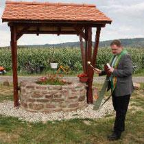 Pfarrer Thomas Dempfle weiht den Brunnen