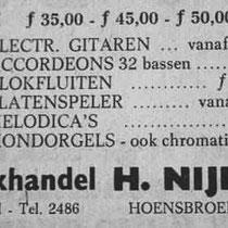 Bij muziekwinkel Nijholt in Hoensbroek op zoek gaan naar een electrische gitaar.