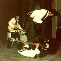 Andy, achter de rug spelend op de bas van de op de grond liggende Ponthon