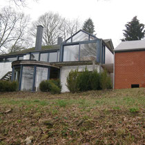 … et le garage en briques rouges à droite. Terrain en pente.