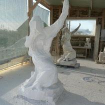 Le volume est d'abord dégrossi à la meuleuse. Le sculpteur coupe la pierre au disque pour l'enlever ensuite au burin.
