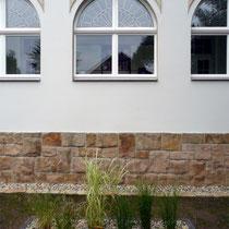 Blick in den Vorgarten mit eingefassten Pflanzflächen und Hainbuchenhecke am Zaun