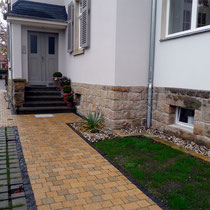 Der erneuerte Hauszugang aus Beton-Pflaster kombiniert mit einer Basaltpflasterkante.
