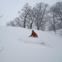 尾根の左手の軽い雪の中を雪煙あげて!