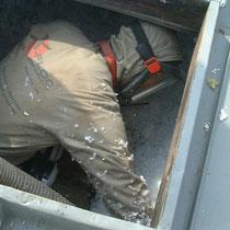Einblasfachmann mit Overall u. Gebläsemaske beim Aufblasen der Dämmung