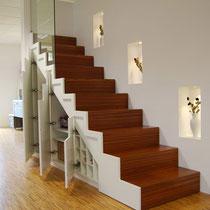 weiße Treppe mit eingebauten Schränken als Stauraum