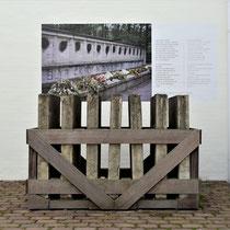 73) Met teer bekladde panelen (onherstelbaar) van het monument bij de fusilladeplaats in het bos met foto en gedicht