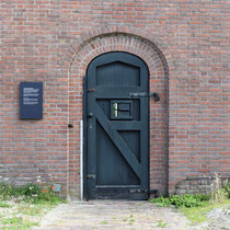 Buitenmuur van binnenaf gezien met de poort die gebruikt werd om de ter dood veroordeelde gevangenen weg te voeren naar de Waalsdorpervlakte waar men gefusilleerd werd
