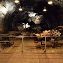 Zicht op opgeblazen ingang van tunnel A - met restanten van een V1 raket rechts en links de kar waarmee de raket werd vervoerd