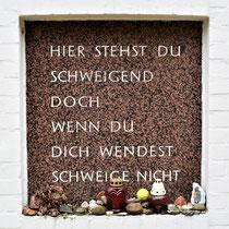 Een gedenksteen aan de muur in de rozentuin