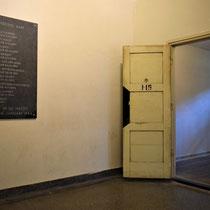 60) Zicht op cel 115 (reconstructie) met herdenkingsplaquette aan muur - Voorheen lijkenruimte 2