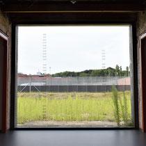 Een van de ramen met zicht op de locatie van voormalige cellenblokken inclusief nummers van de gevangenen