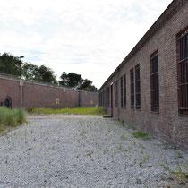 Buitenruimte met rechts het cellencomplex en links de buitenmuur met de toegangspoort op de oorspronkelijke locatie