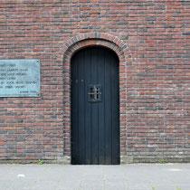 Buitenmuur van buitenaf gezien met de poort die gebruikt werd om de ter dood veroordeelde gevangenen weg te voeren naar de Waalsdorpervlakte waar men gefusilleerd werd