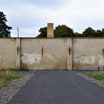 Muur kamp met schoorsteen crematorium achter de muur