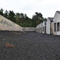 Links achter in het kamp achter de werkbarakken - originele muur