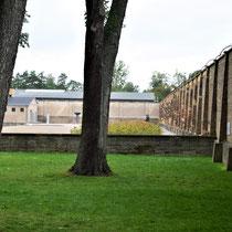 Zicht op muur bij uitgang Siemenskamp - eerste stuk staan en hangen herdenksstenen - links op foto achter de bomen het crematorium