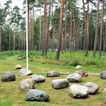 Gedenkplaats met stenen - op de achtergrond portretten van overlevenden