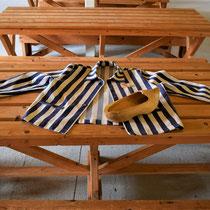 34) Tafel in eetzaal met jas en klomp van gevangene