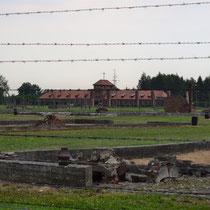 Restanten houten barakken Birkenau - met tweede uitkijktoren op achtergrond