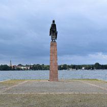 Monument bij meer met zicht op de stad