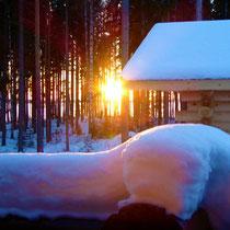 Aus der dampfenden Blockhaussauna am Haus oder aus dem Wohnzimmer am Kamin in den Sonnenuntergang und auf die Weite der Winterlandschaft am gefrorenen See schauen.