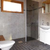 Ebenerdige Dusche, WC, Waschbecken, Spiegelschrank, genügend Ablageflächen.
