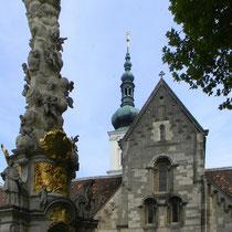 Romanische Westfassade der Stiftskirche (1187) mit Dreifaltigkeitssäule (1729-1739)