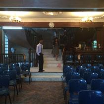 Blick vom Podium auf die frontalen Stuhlreihen und die geschwungenen Treppen, die in den ersten Stock führen.