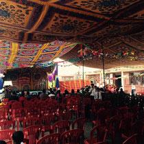 Vor der Bühne befinden sich viele Stuhlreihen, die allesamt überdacht wurden.