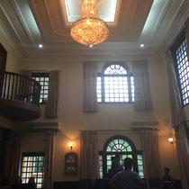 Das Foyer wird als Kapelle genutzt. Ein Teil der Stuhlreihen befindet sich frontal vom Podium, ein anderer seitwärts.
