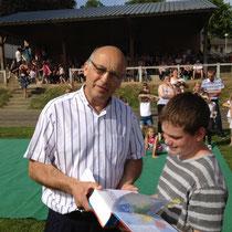 M. Lecourt, maire, remet son dictionnaire à un enfant de CM2