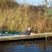 Angela im Faltboot beim Schneiden der Rohrkolben