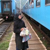 Eine Frau verkauft Obst und Gemüse an Zugpassagiere.