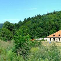 Die Barbara-Hütte - im Hintergrund links der Berg Plešivec mit seiner keltischen Burgstätte die ein Zentrum der Bronzeherstellung war.