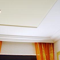 Edle Stuckprofile, LED-Einbaustrahler, integrierte Deckenkarniese und farblich unterteilte Deckenflächen machen dieses Wohnzimmer zum Highlight.