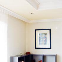 Durch die Stuckdecke und die gedeckten Pastellfarben strahlt dieses Wohnzimmer die gewünschte Gemütlichkeit aus.